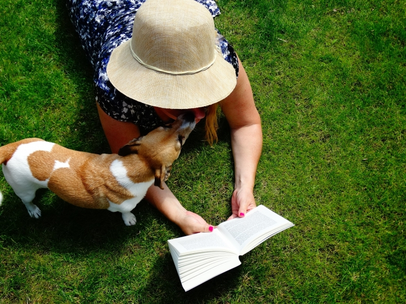 Woman reading outside with dog